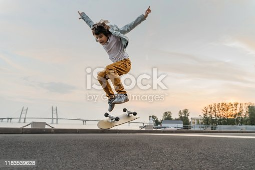 Boy jumping on skateboard at the street. Funny kid skater practicing ollie on skateboard at sunset.