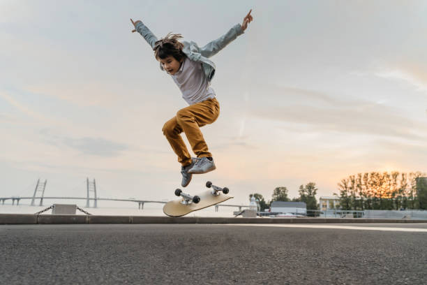boy jumping on skateboard at the street. - skate foto e immagini stock