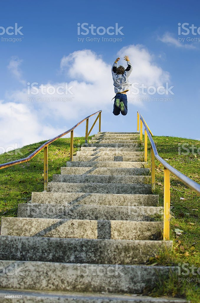 Boy Jumping On Top Of High Outdoor Stairs stock photo