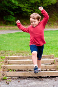 Young boy jumping over obstacle on exercise course