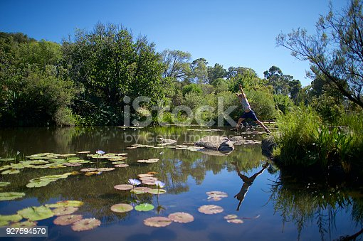 509813720 istock photo Boy jumping over water with reflection 927594570