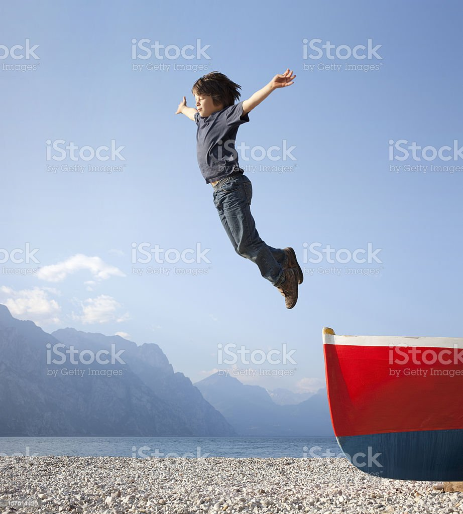 Boy jumps from a boat stock photo