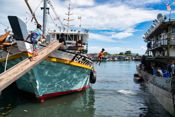 Boy jumps off fishing trawler in Semporna, Sabah stock photo