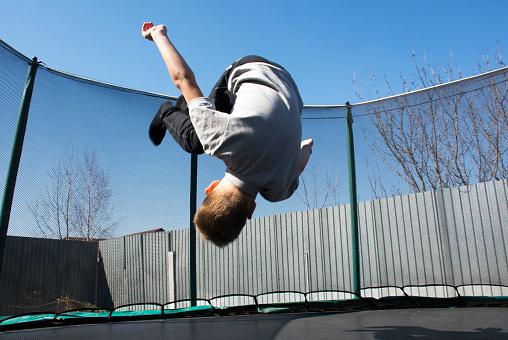 Un Niño Salta En Un Trampolín Hace Un Salto Mortal Saltando En El Trampolín Foto De Stock Y Más Banco De Imágenes De Adolescente Istock