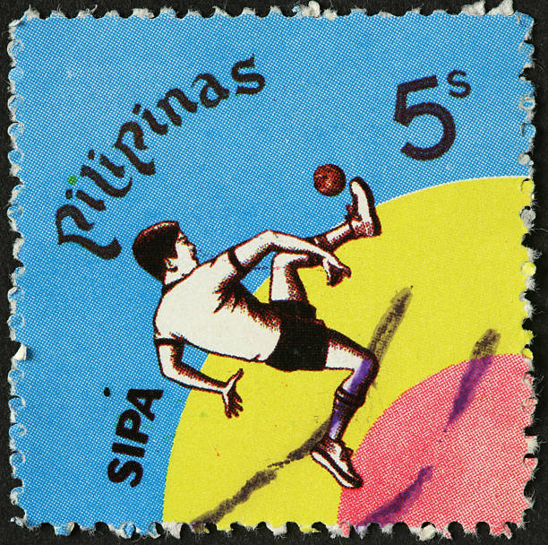 boy kicking a ball on an old Philippine postage stamp stock photo