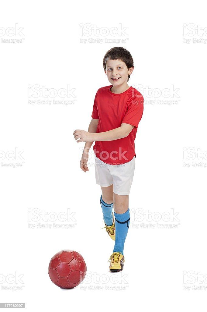 boy kicking a red soccer ball royalty-free stock photo