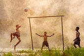 Boy kicking a soccer ball eveningThe sun was falling (Focus on soccer ball)
