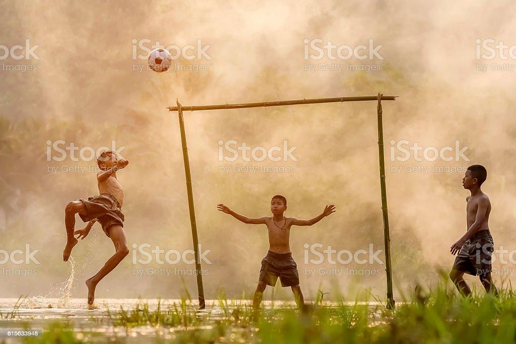 Boy kicking a soccer ball eveningThe sun was falling stock photo
