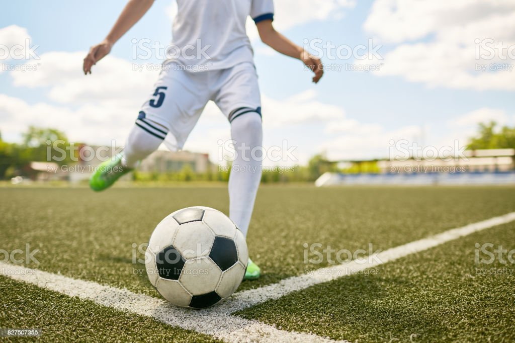 Junge treten Ball auf Fußballplatz – Foto