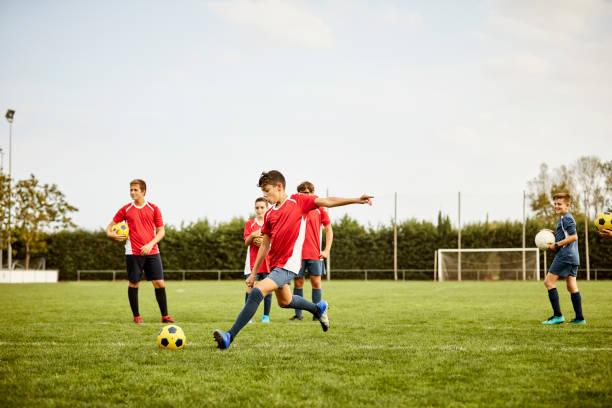 Junge kickt Fußball auf dem Boden während des Trainings – Foto
