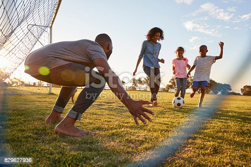 829627936istockphoto A boy kicks a football during a game with his family 829627936