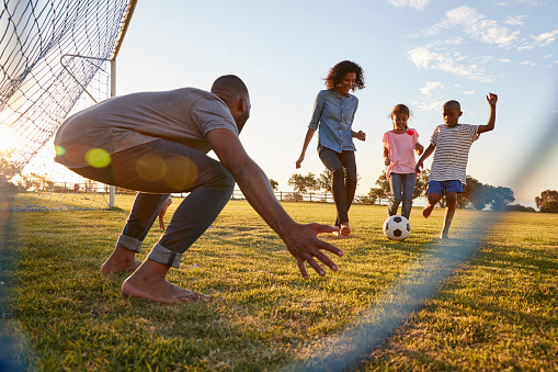 istock A boy kicks a football during a game with his family 829627936