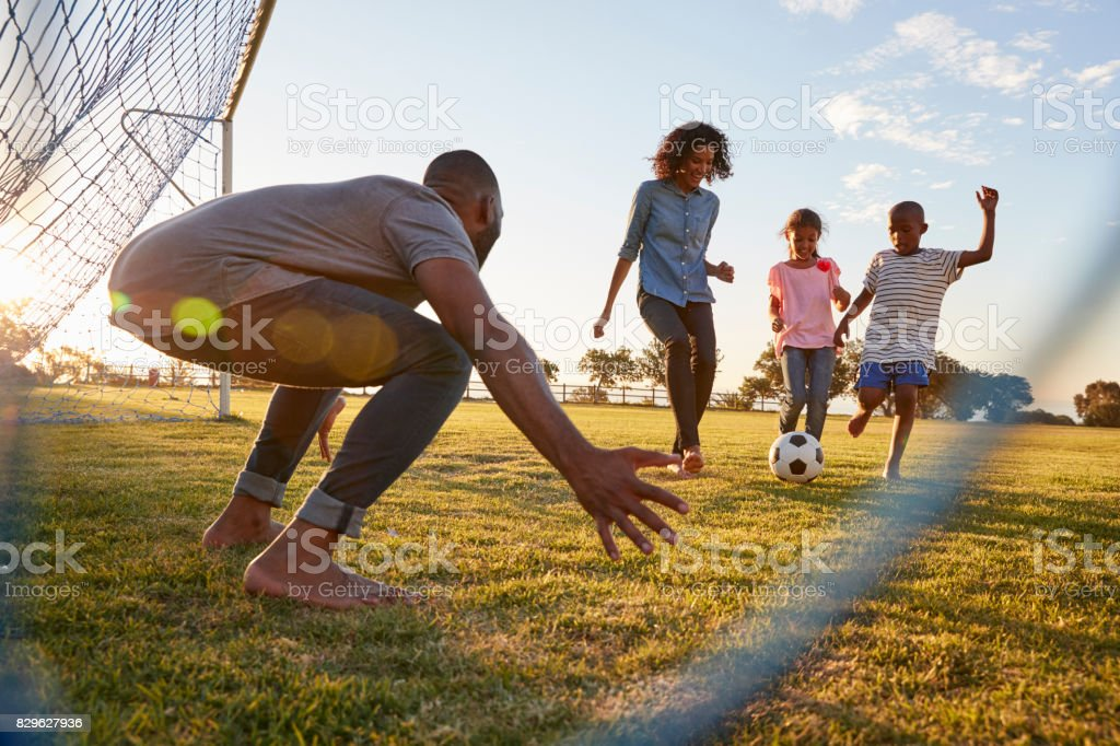 A boy kicks a football during a game with his family - fotografia de stock