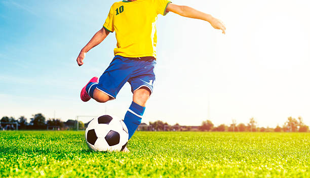Boy kicks soccer ball while playing a football match stock photo