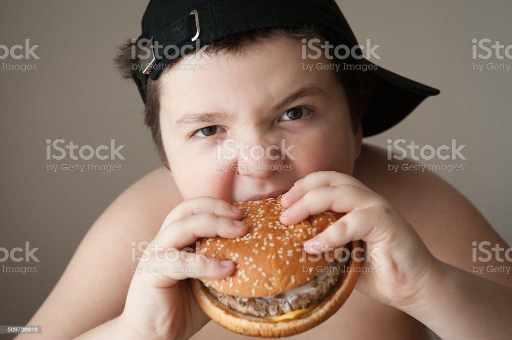 boy kid fat  burger food  health sports cap hungry stock photo