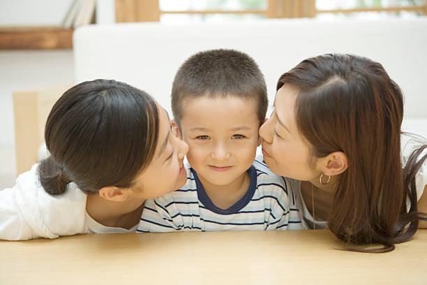 ragazzo baciata da madre e la sorella maggiore - kids kiss embarrassed foto e immagini stock