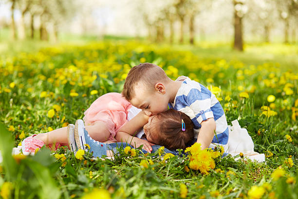 boy kissing a girl - little girls little boys kissing love stock photos and pictures