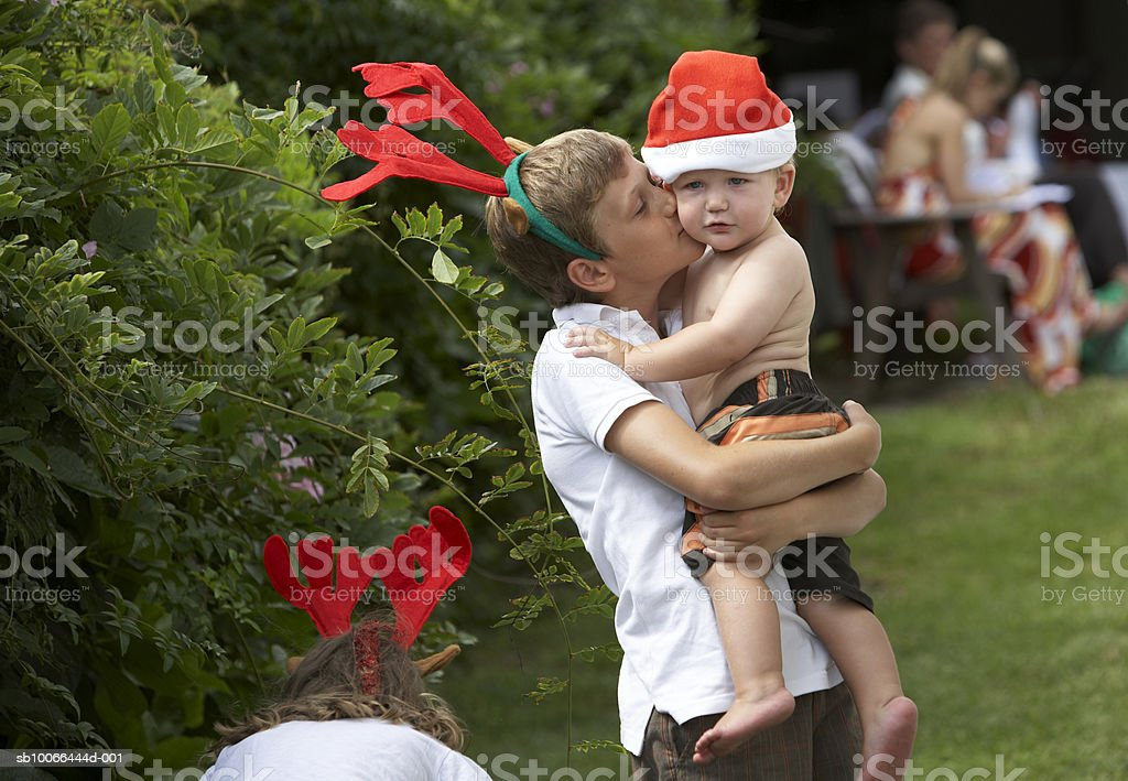 Boy (12-13) kissing brother (16-18 months) on lawn, with Christmas hats 免版稅 stock photo