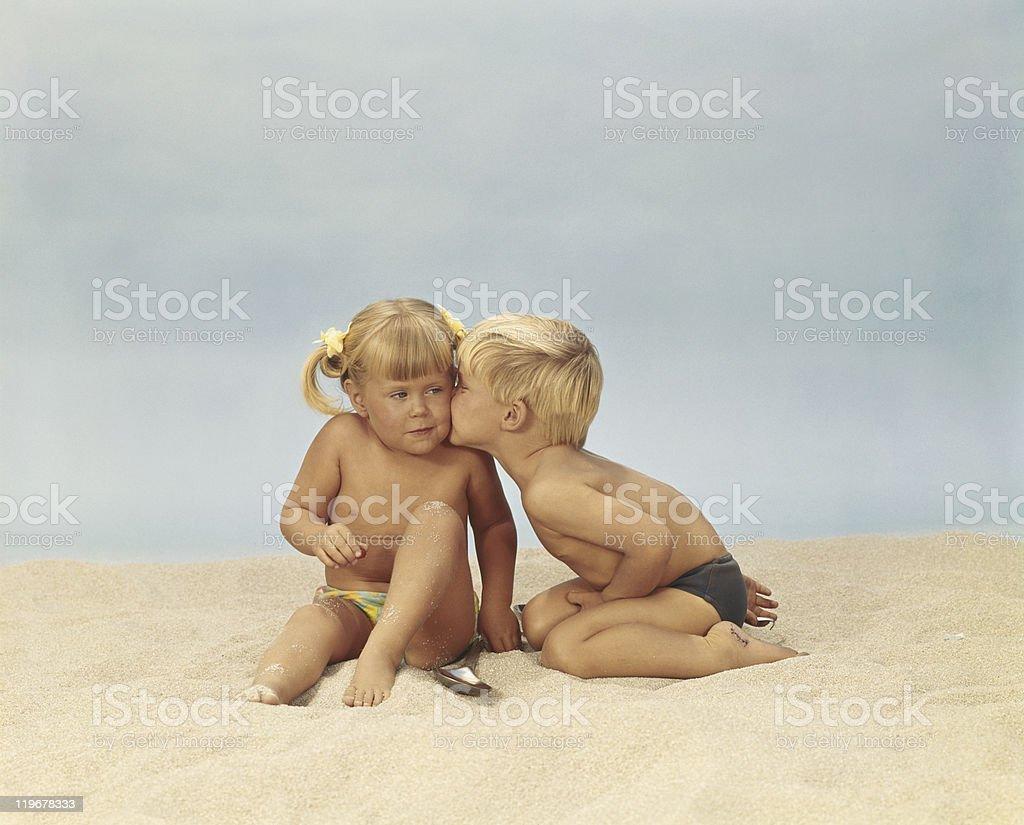 Boy kissing girl on beach stock photo