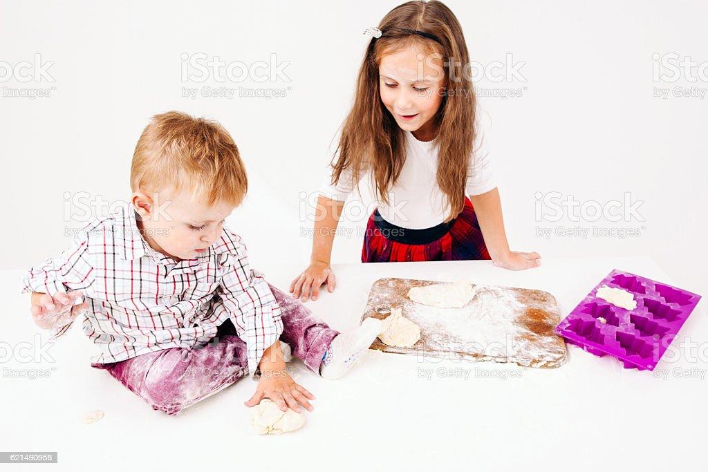 Boy kneading raw dough with his sister Lizenzfreies stock-foto