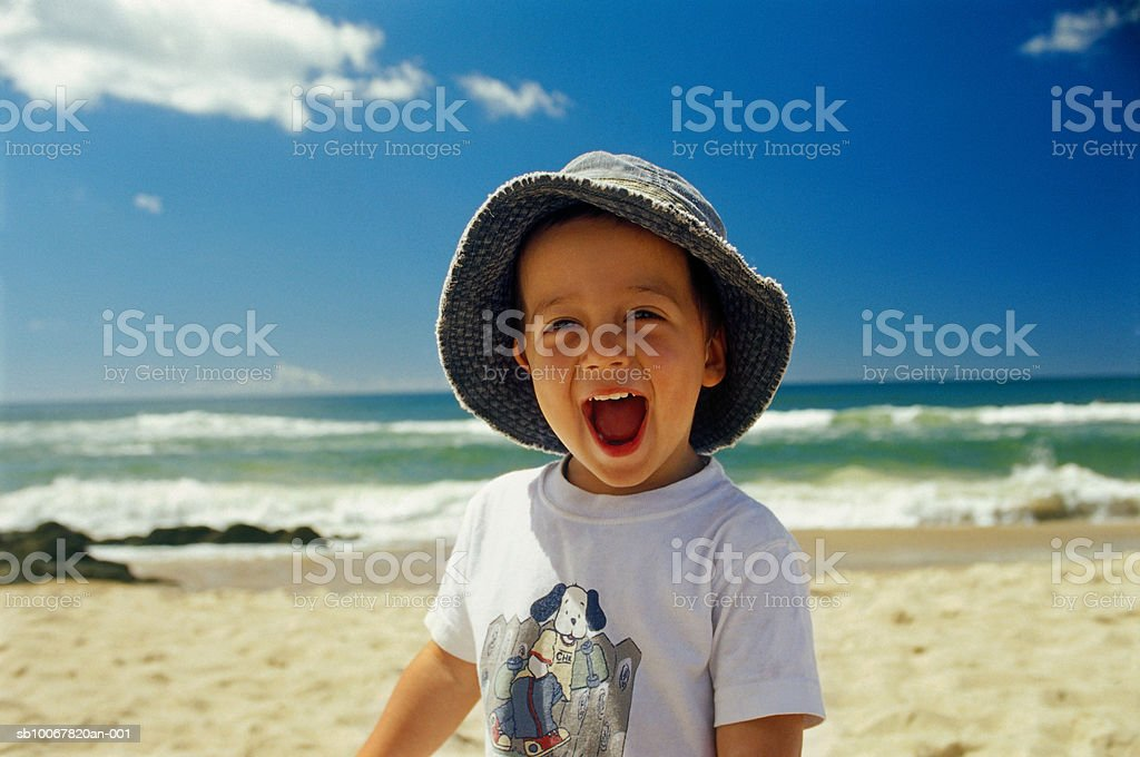 Boy laughing on beach, portrait royalty free stockfoto