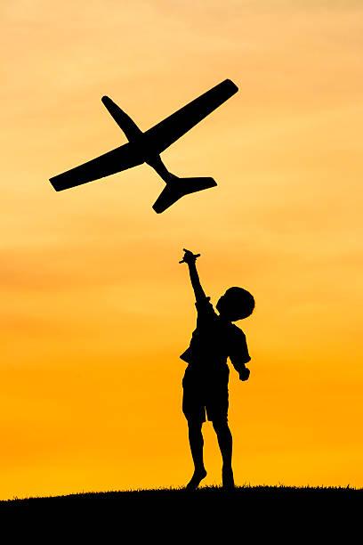 Boy launches toy plane. stock photo