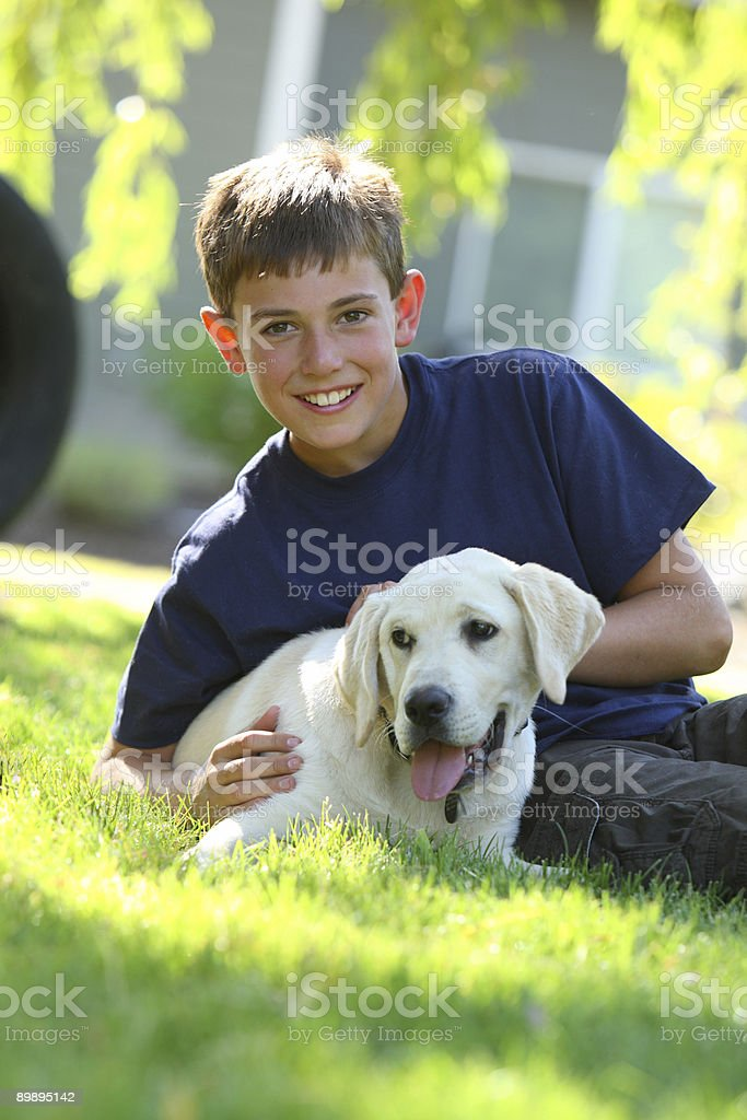Boy sentar en césped con perro mascota foto de stock libre de derechos