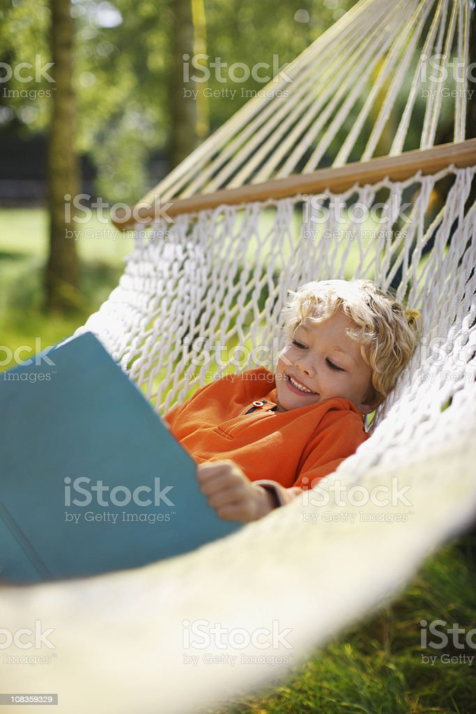 Boy laying in hammock reading book royalty-free stock photo