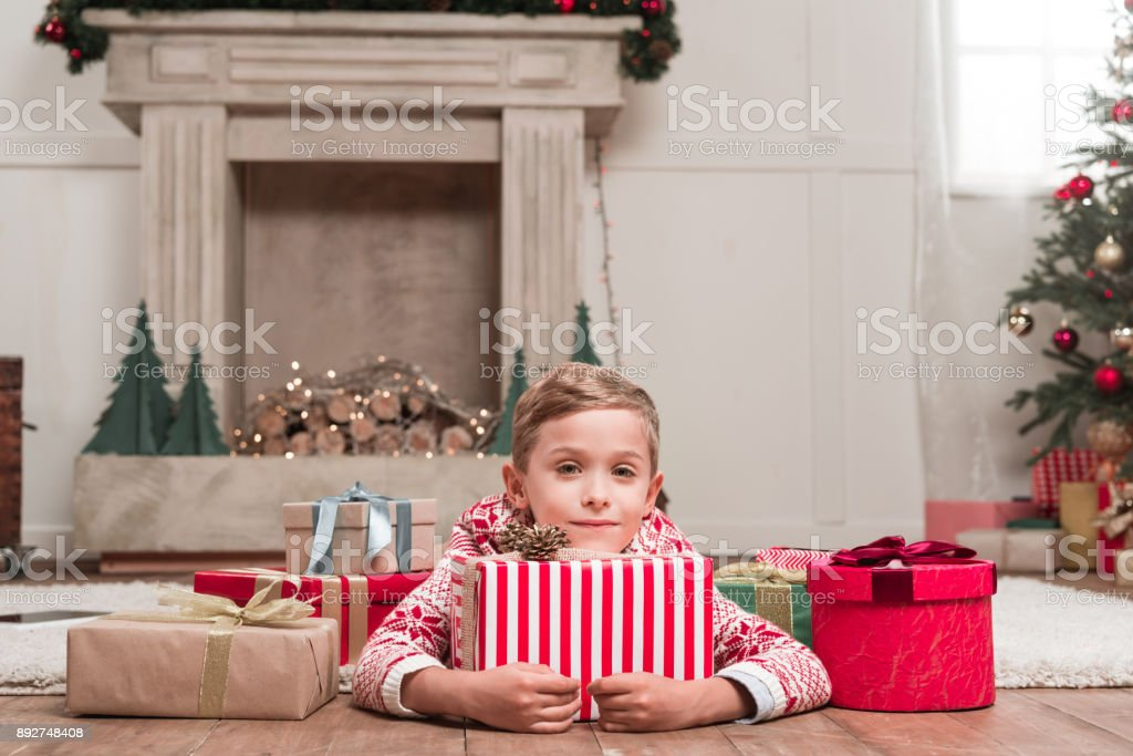 boy laying on floor with christmas gifts stock photo