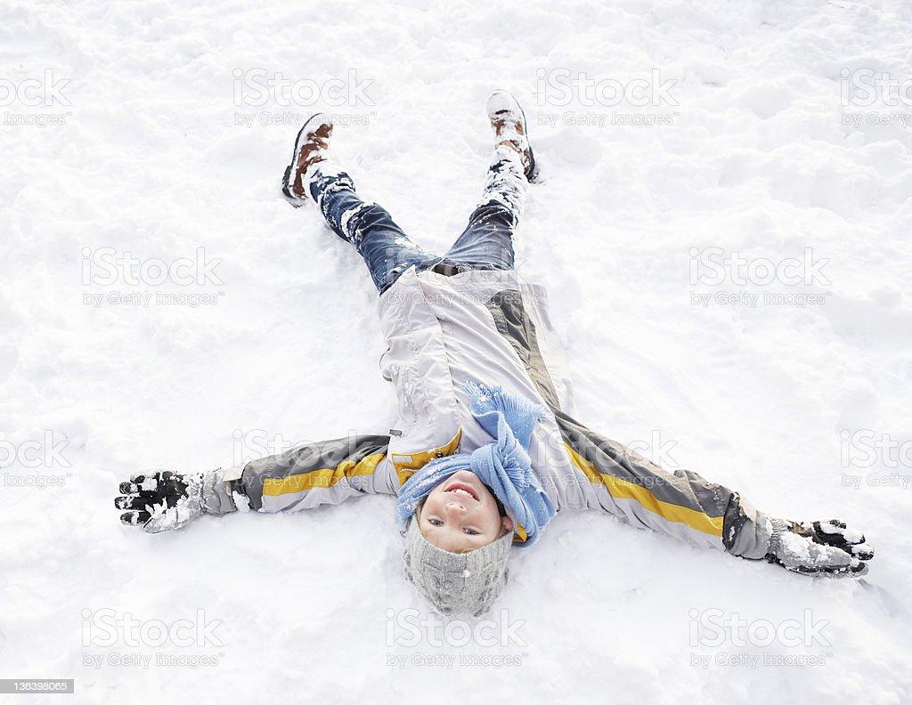 Boy Laying On Ground Making Snow Angel stock photo