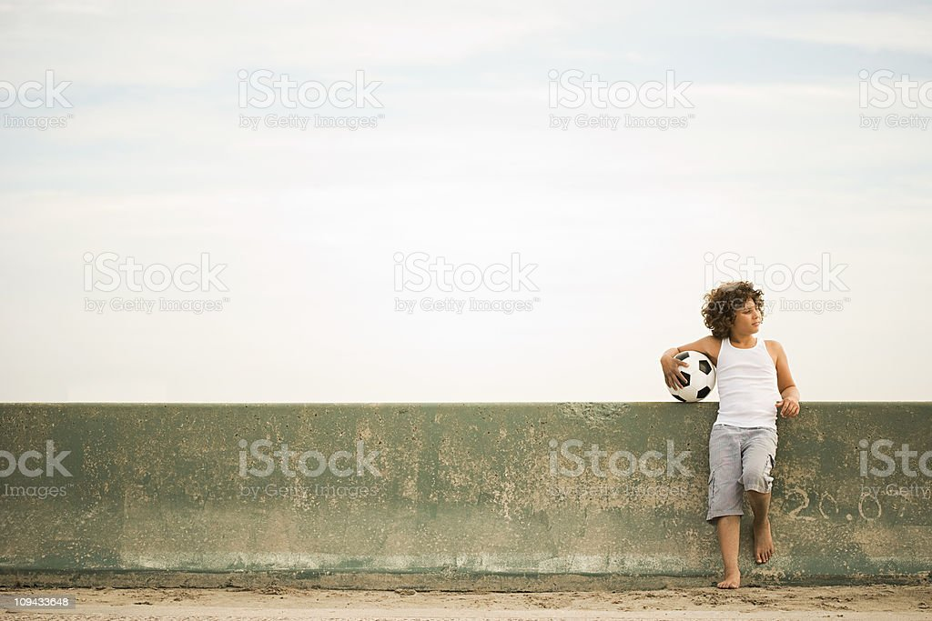 Boy leaning against wall with football stock photo