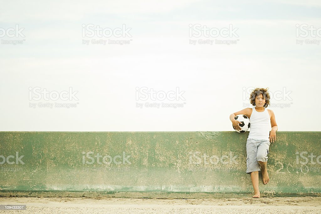 Boy leaning against wall with football, portrait royalty-free stock photo