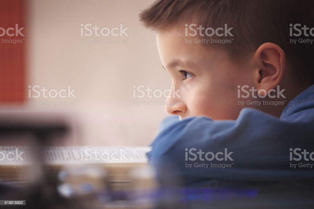Boy leaning on a book and looking stock photo