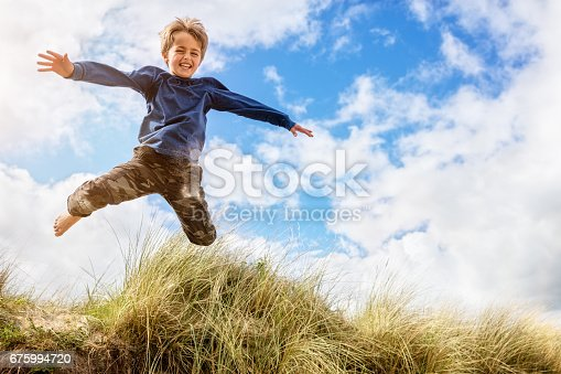 istock Boy leaping and jumping over sand dunes on beach vacation 675994720
