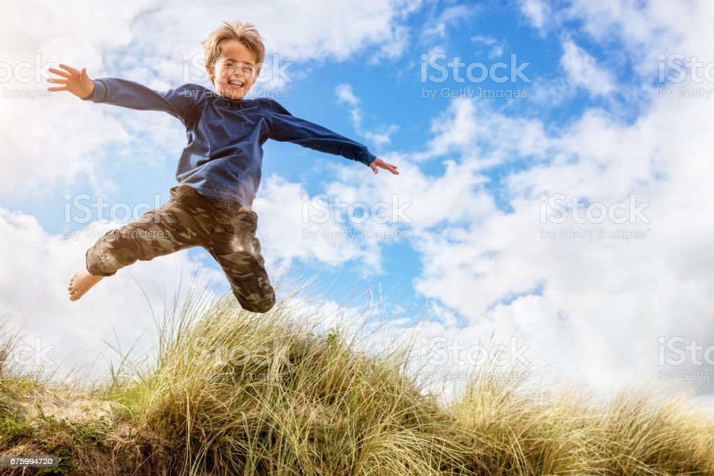 Boy leaping and jumping over sand dunes on beach vacation stock photo