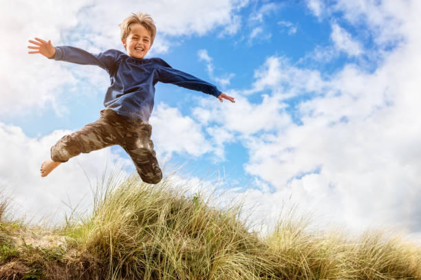 Boy leaping and jumping over sand dunes on beach vacation - foto de stock