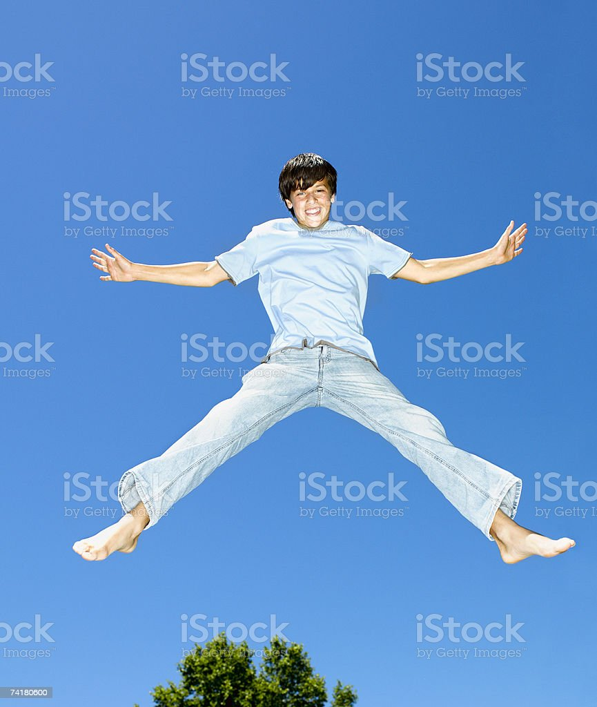 Boy leaping outdoors with blue sky and trees royalty-free stock photo
