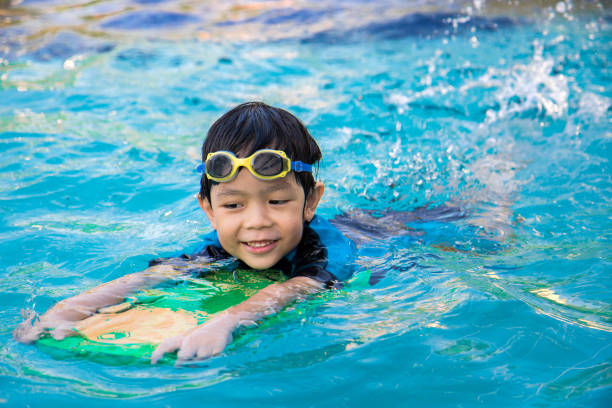 boy learn to swim in the swimming pool - swimming stock pictures, royalty-free photos & images
