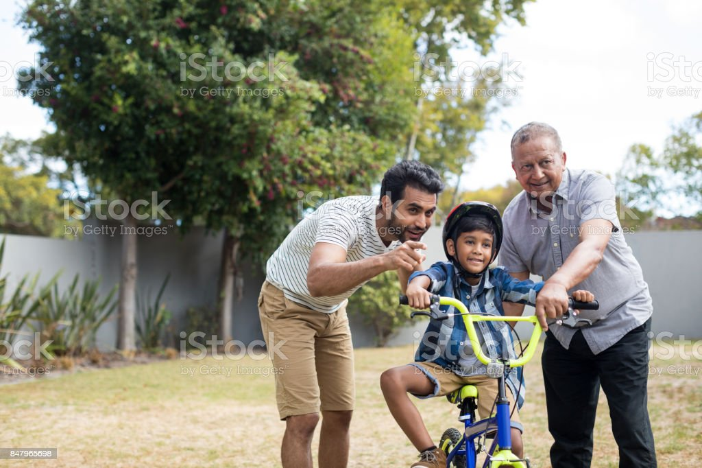 Boy learning bicycle with father and grandfather stock photo