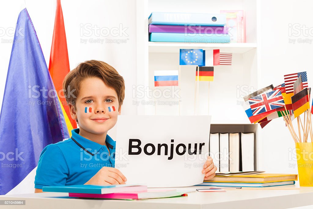 Boy learning French sitting at desk in classroom stock photo