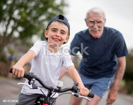 853720192 istock photo Boy learning how to ride a bike from his grandfather 481523506