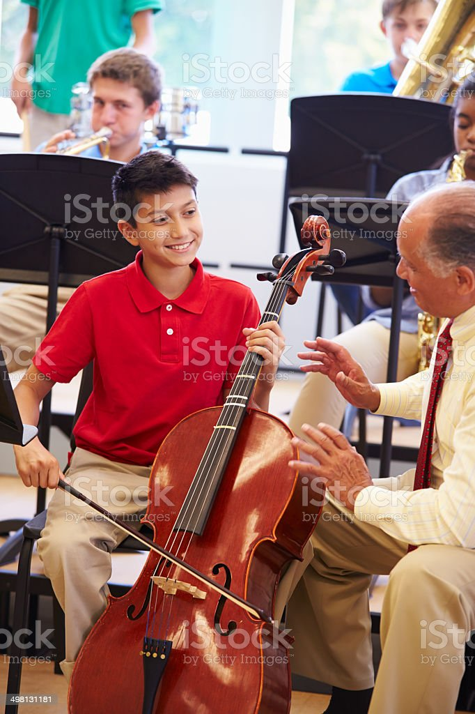 Boy Learning To Play Cello In High School Orchestra stock photo