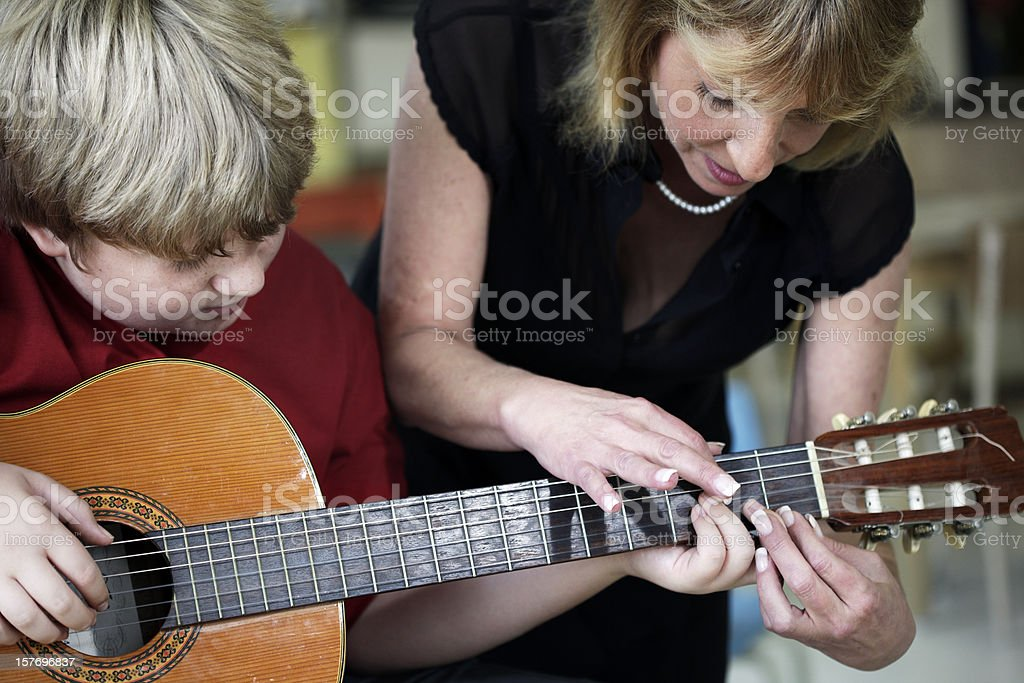 Boy Learning to Play Guitar in Music Class stock photo