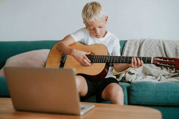 Boy learning to play guitar through a video call with his teacher Boy learning to play guitar through a video call with his teacher eastern european descent stock pictures, royalty-free photos & images