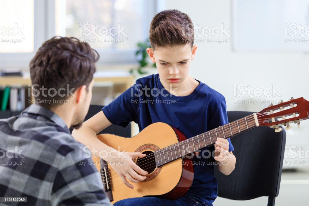 Boy learning to play guitar with instructor Boy learning to play guitar with instructor at conservatory. Male teacher is sitting with pre-adolescent guitarist. They are in classroom. 12-13 Years Stock Photo