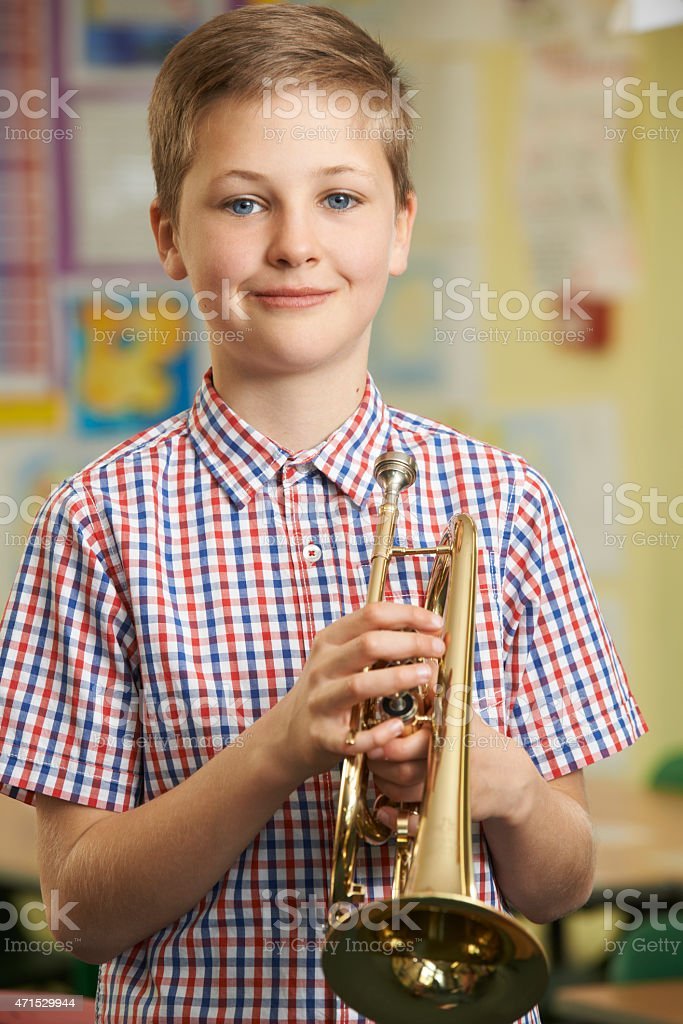 Boy Learning To Play Trumpet In School Music Lesson stock photo