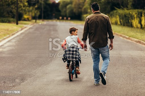 kid learning to ride a bicycle on an empty road. Rear view of a boy riding a bicycle while his father walks along with the kid.