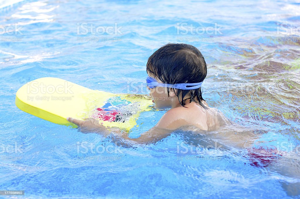 Boy learning to swim stock photo