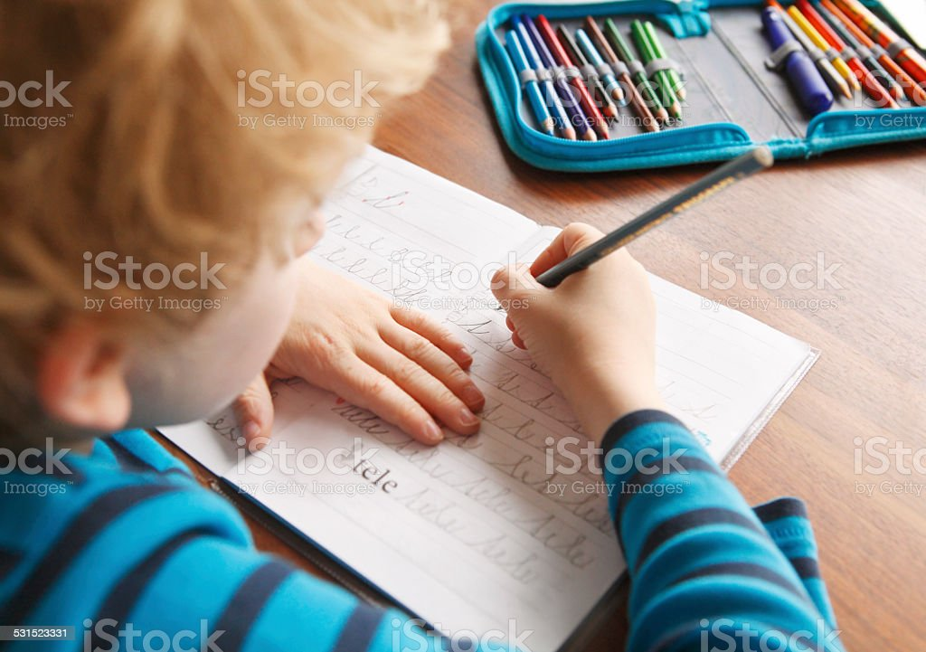 Boy learning to write alphabet characters stock photo