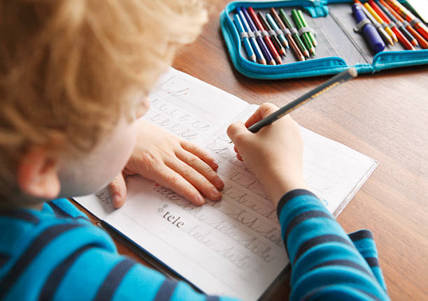 Boy learning to write alphabet characters Boy learning to write alphabet characters at school workbook stock pictures, royalty-free photos & images